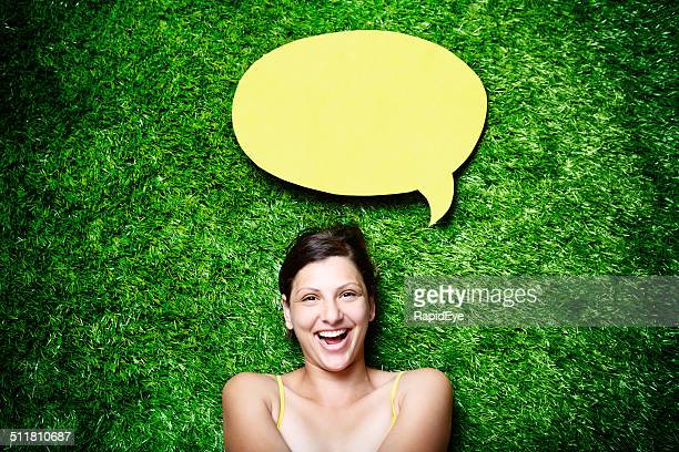 Pretty, laughing brunette lying on grass with blank speech bubble