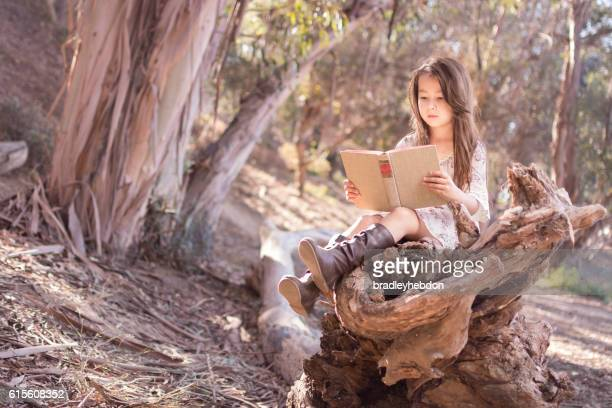 Pretty little girl outdoors quietly reading a book