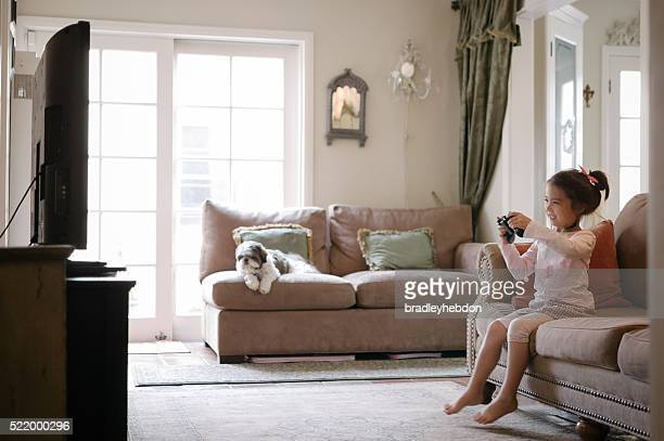 Jolie petite fille jouant à un jeu vidéo à la maison