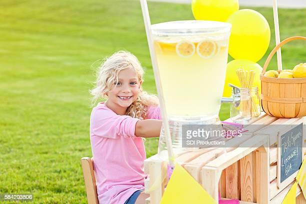 Pretty little girl smiling at her lemonade stand