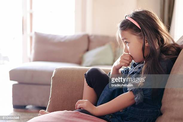 Pretty little girl watching TV on the couch