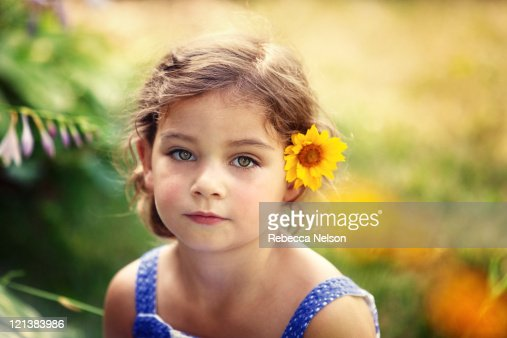 pretty little girl with yellow flower in her hair stock