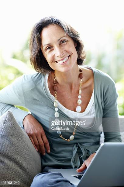 Pretty, mature woman sitting at home with laptop