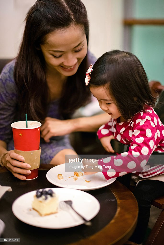 pretty mom & baby having coffee & cake in cafe : Stock Photo