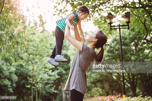 Pretty mom & child playing joyfully in park