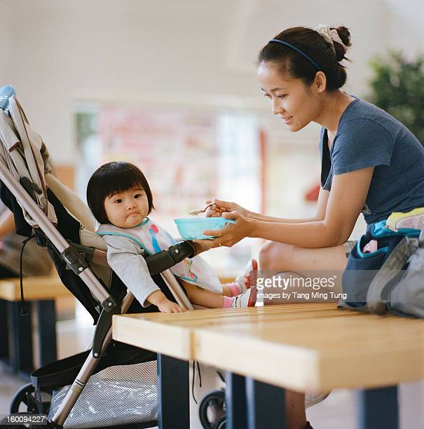 Pretty mom feeding baby cereal with milk in mall