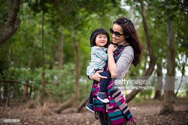 Pretty mom holding baby in the trees joyfully