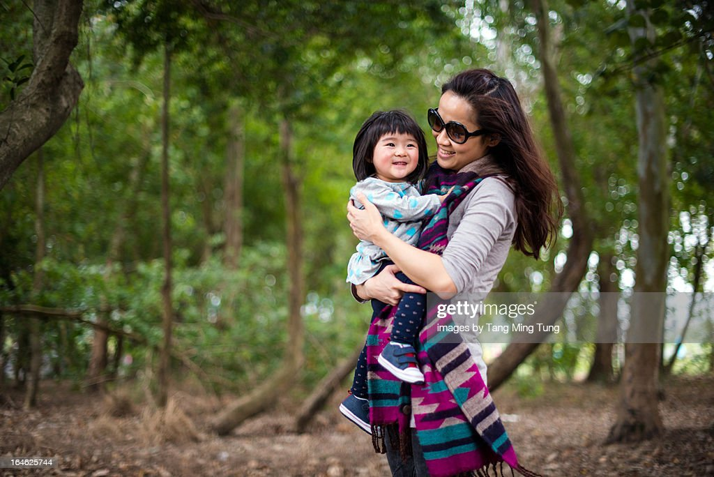 Pretty mom holding baby in the trees joyfully : Stock Photo