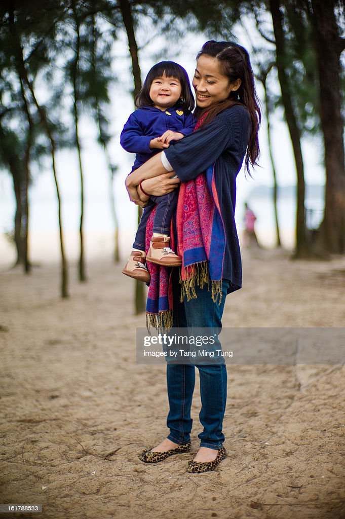 Pretty mom holding baby on beach smiling joyfully : Stock Photo