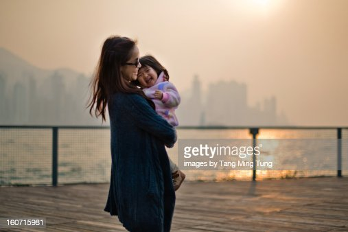 Pretty mom holding laughing baby on a dock : Stock Photo