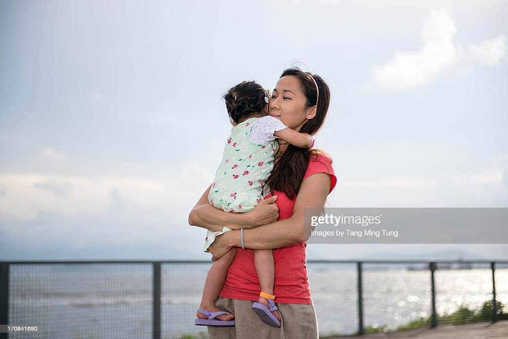 Pretty mom holding toddler in her arms with love : Stock Photo