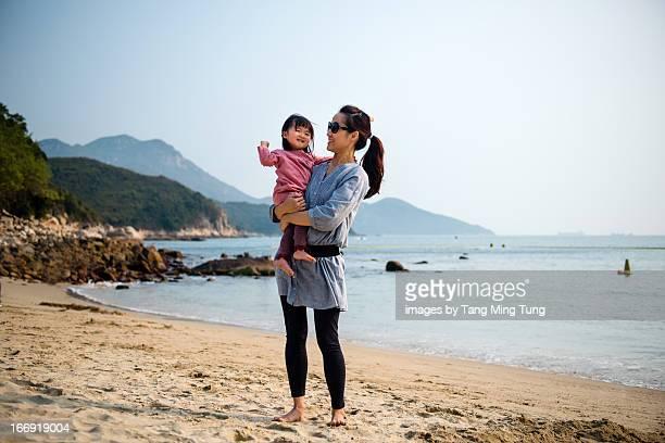 Pretty mom holding toddler on beach joyfully