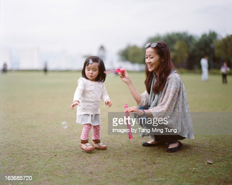 Pretty mom playing bubble stick with toddler girl : Stock Photo