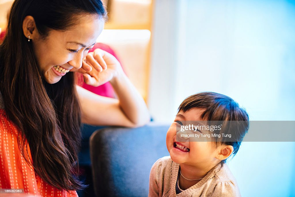 Pretty mom talking to toddler girl joyfully : Stock Photo