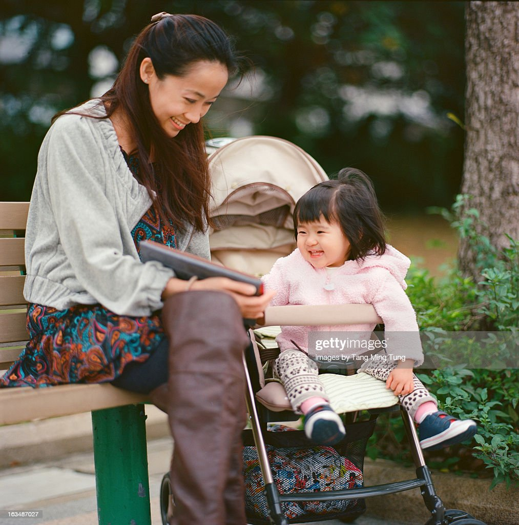 Pretty mom & toddler girl playing tablet joyfully : Stock Photo