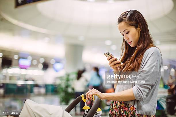 Pretty mom using smartphone in shopping mall