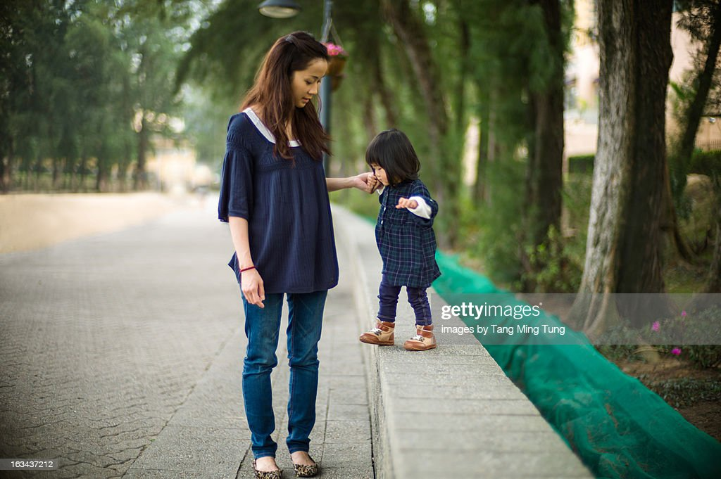 Pretty mother holding toddler girl's hand walking : Stock Photo