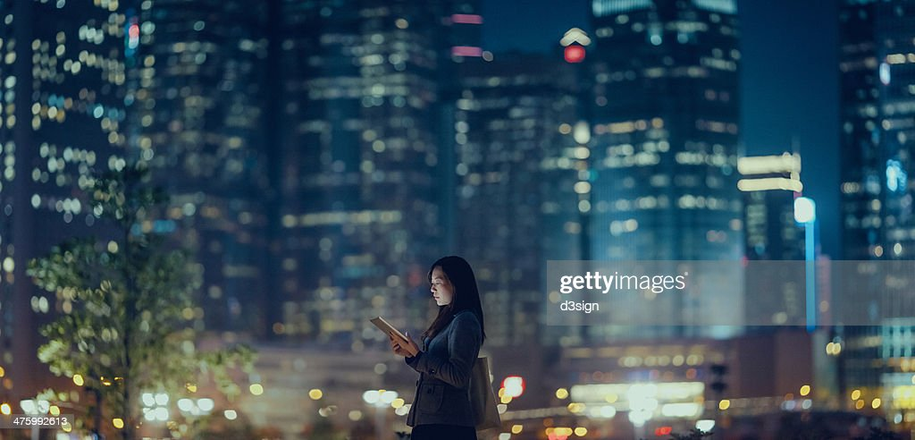 Pretty office lady is using tablet in city : Stock Photo