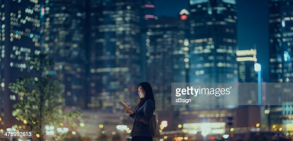 Pretty office lady is using tablet in city : Stockfoto
