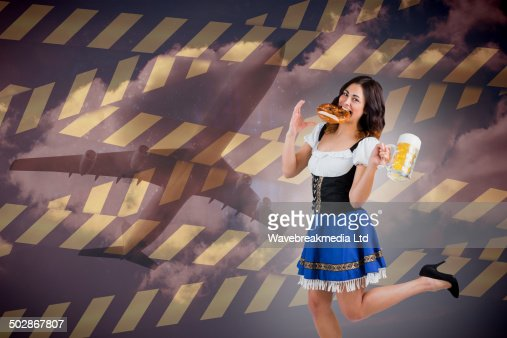 Composite image of pretty oktoberfest girl holding beer tankard and pretzel : Stock Photo
