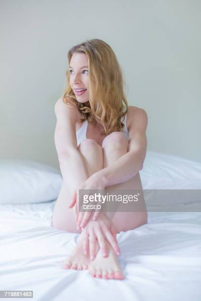 Pretty pensive blonde woman sitting in bed