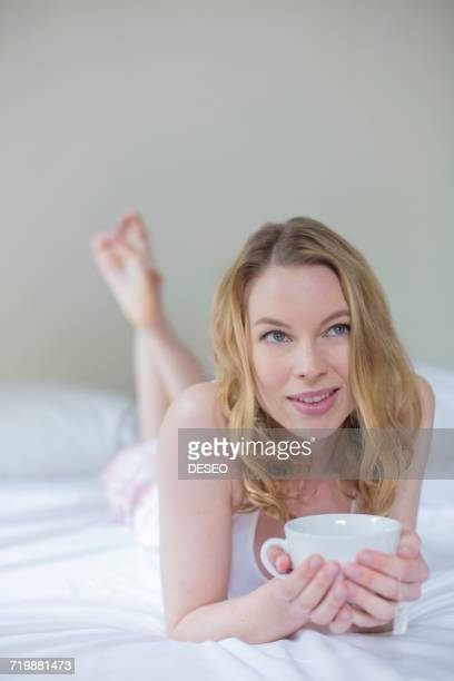 Pretty pensive blonde woman with a cup of tea in bed