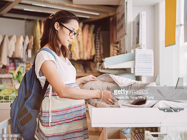 Pretty pregnant lady shopping for baby's beddings