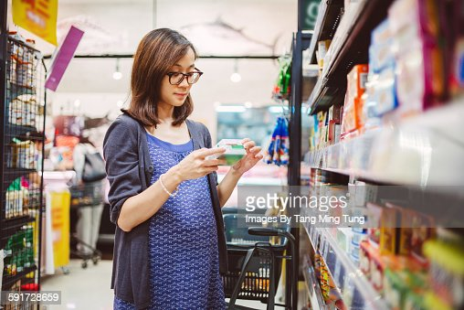 Pretty pregnant lady shopping in a grocery store.