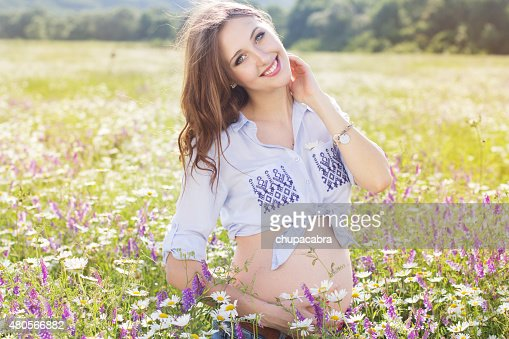 Pretty pregnant woman in daisy flowers field : Stock Photo