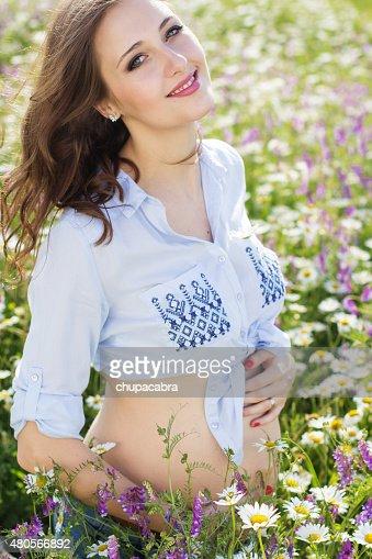 Pretty pregnant woman in daisy flowers field : Stock Photo