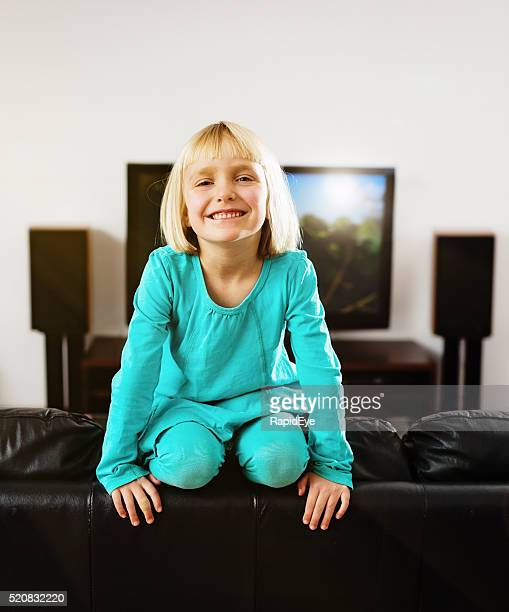 Pretty pre-school girl perches on couch at home, smiling