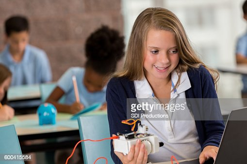Pretty preteen girl programming robot in STEM education class