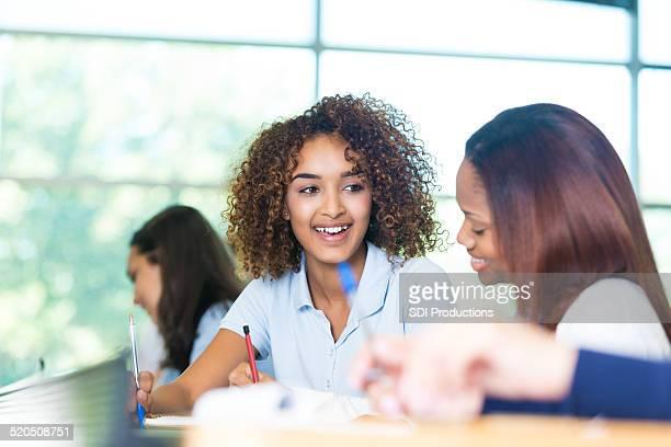 Bella ragazza di scuola secondaria privata parla di un amico in aula