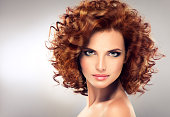 Pretty red haired girl with curls , fashionable makeup. Straight look on camera.
