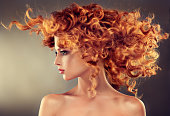 Pretty red haired girl with curly hairstyle.Flying hair in dynamic movement.