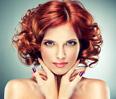 Pretty red haired girl with curls , fashionable makeup and violet manicure.  Charming look.