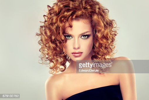 Pretty red-haired girl with curls. : Stock Photo