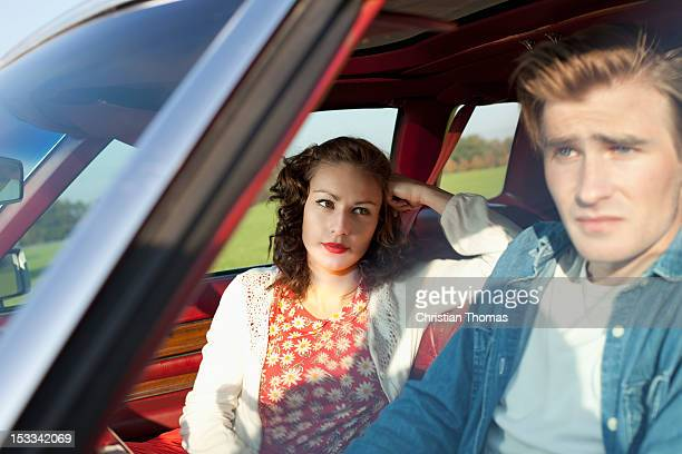 A pretty rockabilly girl looking at her boyfriend in irritation while sitting in vintage car