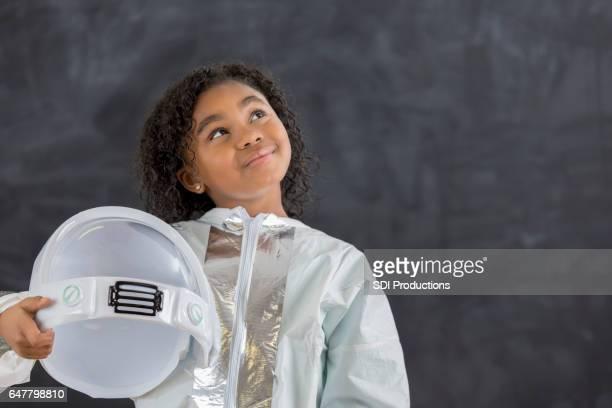 Pretty schoolgirl in astronaut costume