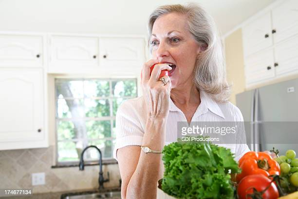 Pretty Senior Adult Woman Eating an Apple in her Kitchen