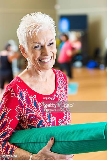 Pretty senior woman before yoga class at senior center