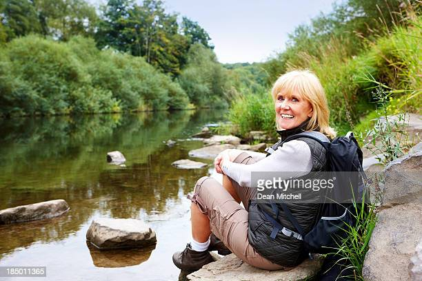 Pretty senior woman sitting on rocks by the river