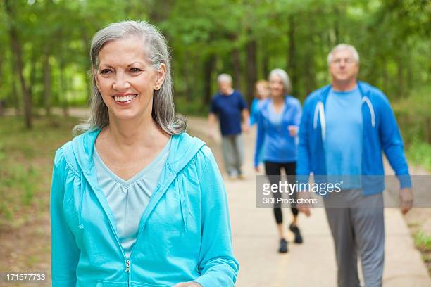 Pretty senior woman walking in park with exercise group
