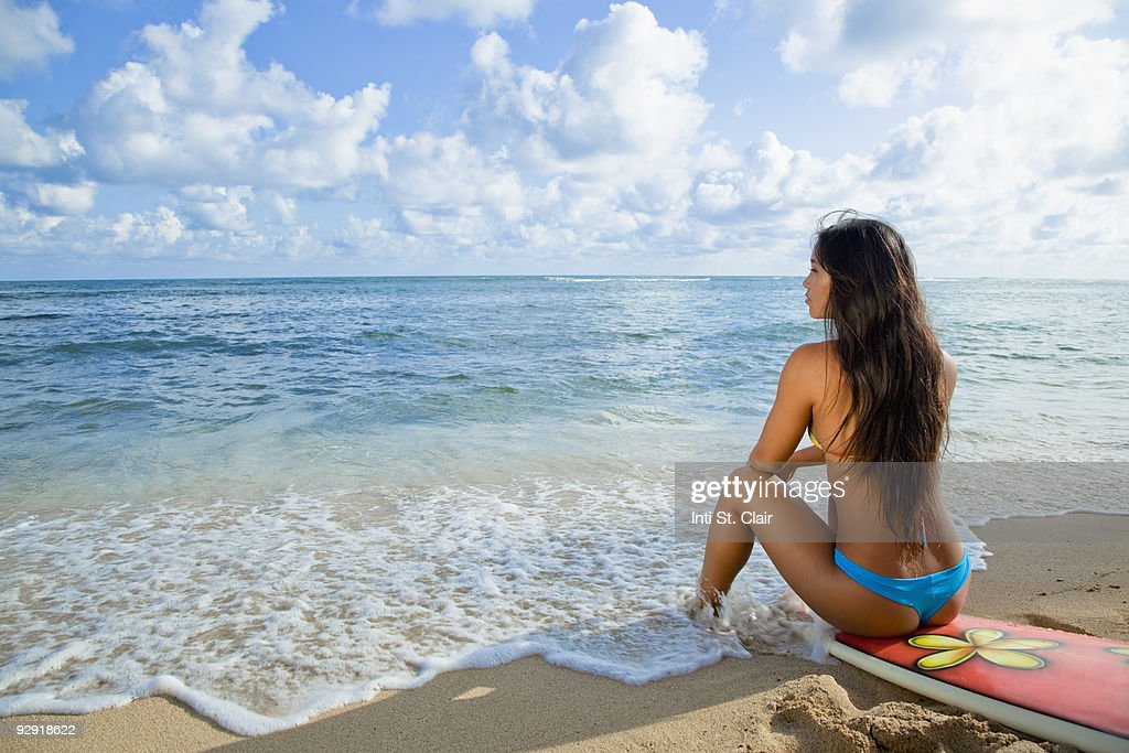 Pretty, sexy girl sitting on surfboard on beach : Stock Photo