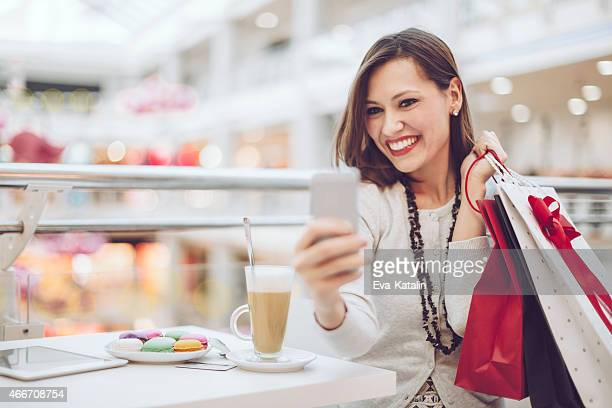Pretty shopper taking selfies with her cell phone