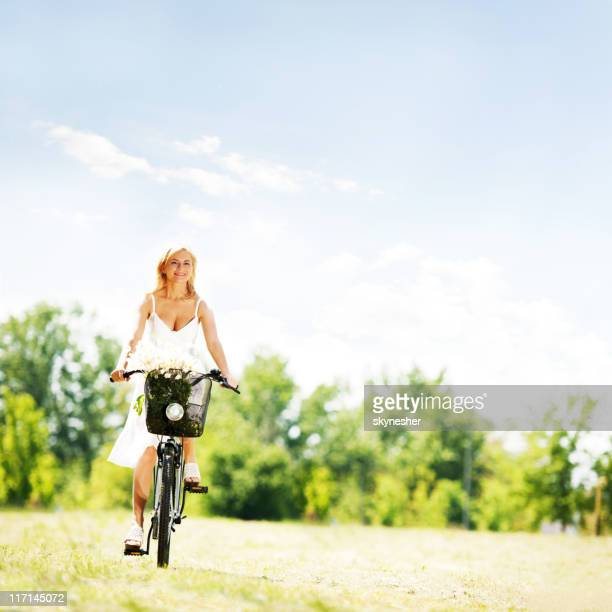 Pretty smiling blonde riding a bike.