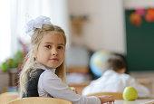 Pretty smiling schoolgirl in class