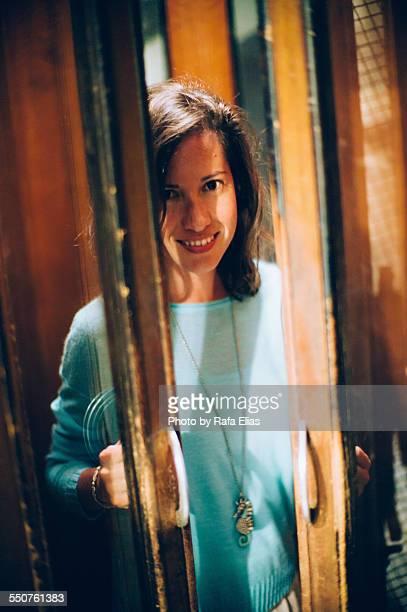Pretty smiling woman behing crystal doors