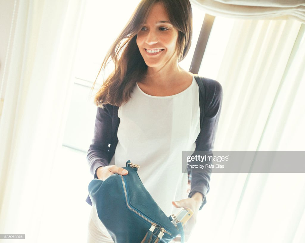 Pretty smiling woman holding purse indoors