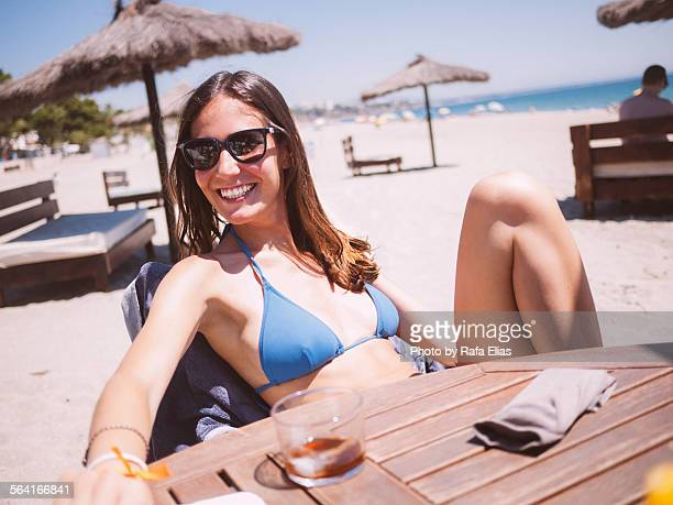 Pretty smiling woman in bikini at the beach bar